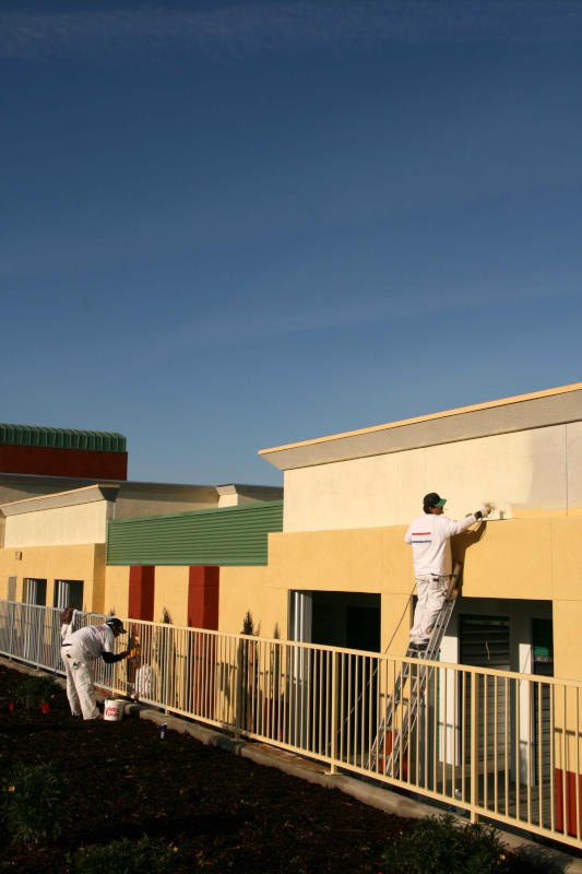 Professional painting crew doing a paint job at a strip mall