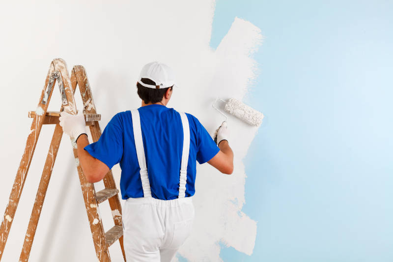 Painter on a ladder using a paint brush